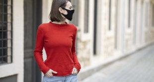 Mulher caminha pela rua no afrouxamento das medidas de isolamento contra a Covid-19 e se preocupa em relação a reinfecção