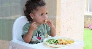 Bebê consome alimentos sob observações dos pais que procuram reduzir o seu consumo de açúcar antes do tempo.