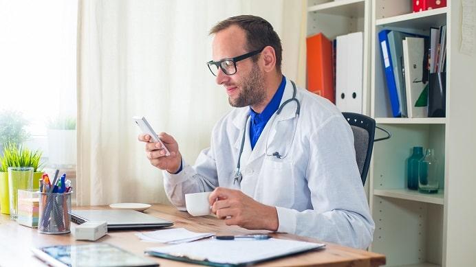 médico olhando celular antes de realizar uma consulta por telemedicina