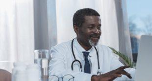 médico usando whitebook no laptop