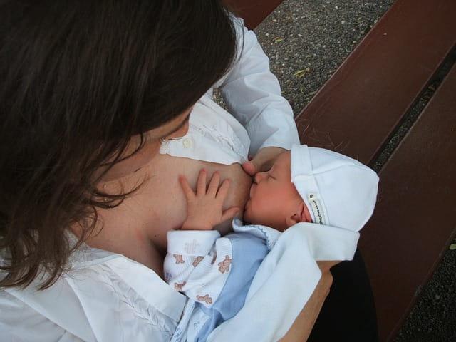 Mãe com hábitos de prática de atividade física realiza a amamentação do seu recém-nascido.