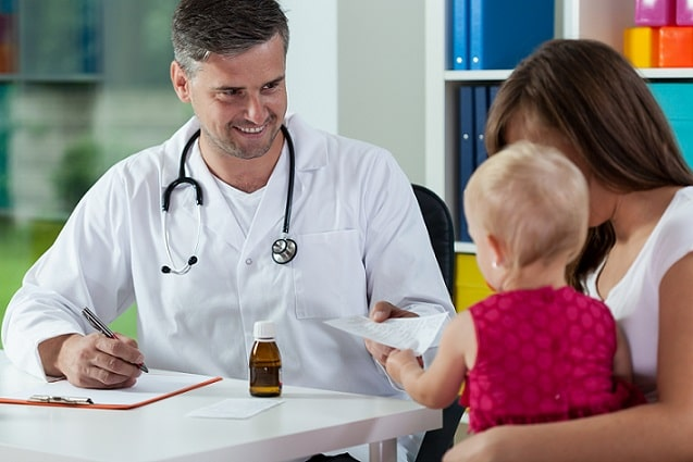 médico conversando com criança e mãe em consulta