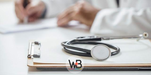 médico escrevendo em prancheta de paciente com pancreatite autoimune