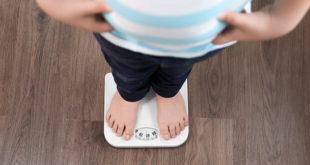 pés de menino com obesidade subindo em uma balança