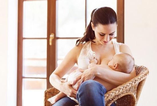 mãe amamentando bebê que faz uso de fórmulas infantis sentada