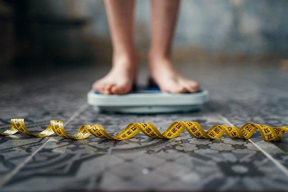 pés em cima da balança verificando obesidade