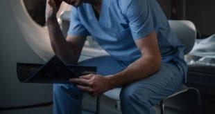 médico com burnout, sentado, após diagnóstico de covid-19 de paciente