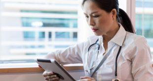 enfermeira consultando o nursebook sobre feridas e ostomias