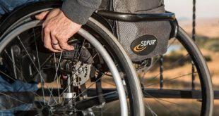 homem segurando a roda de cadeira de rodas
