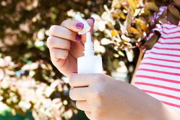 mão de menina segurando escetamina, medicamento intranasal