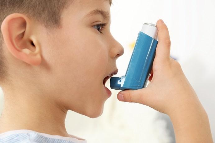 criança usando bombinha por relação de asma e covid-19 em pediatria
