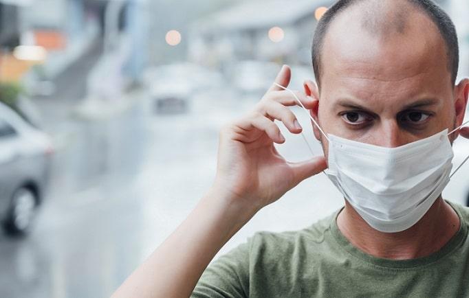 homem colocando máscara por causa de covid e trombose