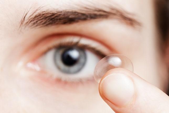 mulher segurando lente de contato