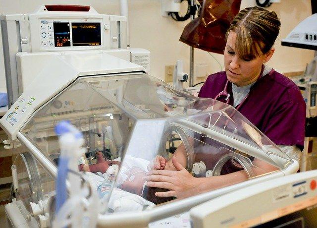 profissional de enfermagem cuidando de bebê independente do piso salarial