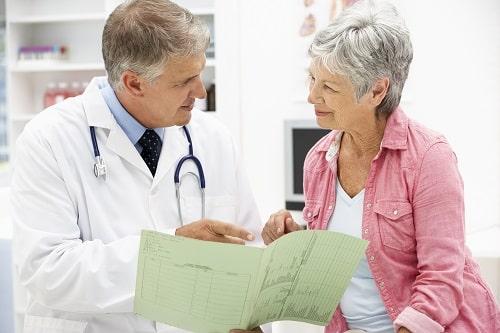 Médico explica as complicações da pós-menopausa para paciente com fratura