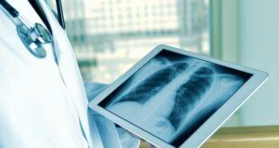 Médico confere no Whitebook conteúdo do Atlas de Radiologia